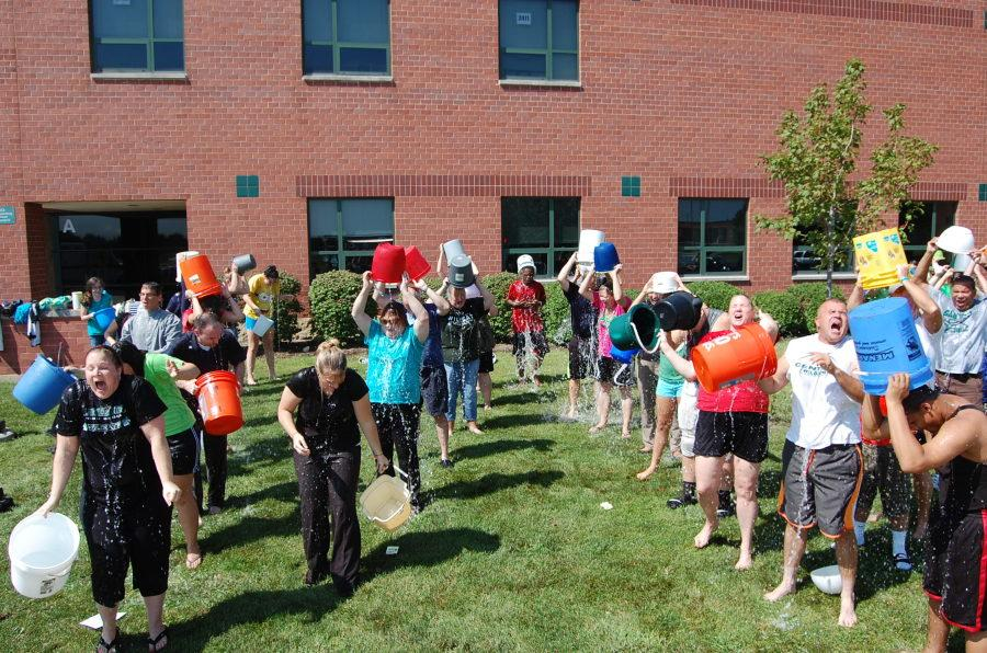 Staff members douse themselves outside of school to raise awareness and money for ALS research.