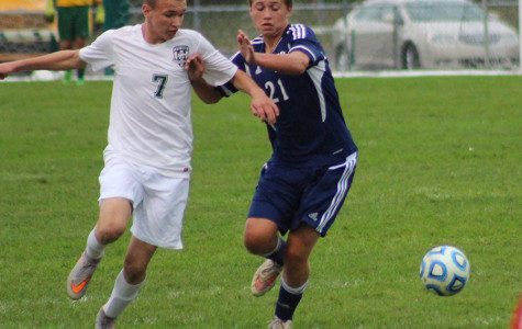 Junior Max Woodward wards off a defender to receive the ball  against Oswego East on Tuesday, Sept. 29.
