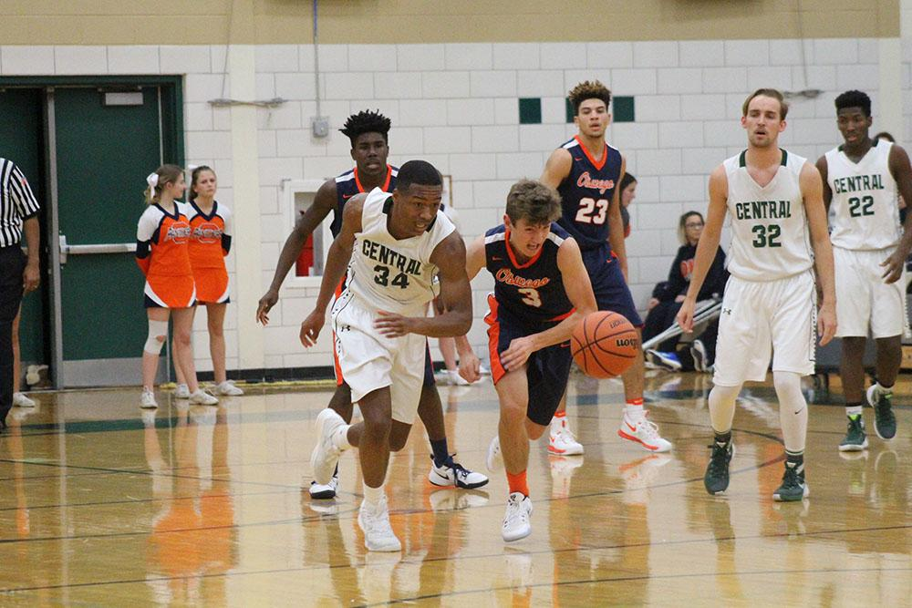 Michael Hood, senior, competes for the basketball against Oswego on  Dec. 2. The team went on to  lose by a close score of  50  to  46.