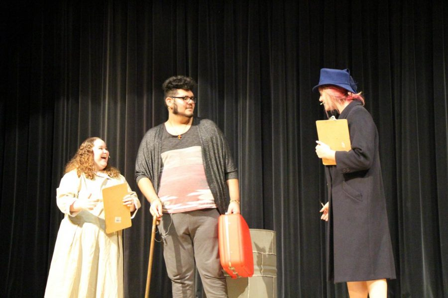 "Seniors Brittney Ebner, Americo Allen Garcia and  Mikayla Icenogle, rehearse the iconic scene where Kris Kringle is hired to be the Macy's Santa Claus in ""Miracle on 34th Street."""