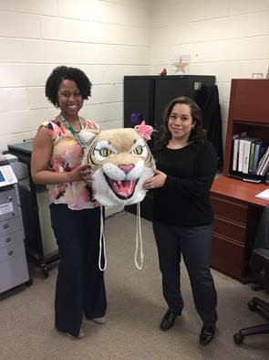 Xiomara Cole passes the Wildcat Head to Sarah Cammack in Student Services.