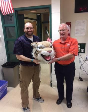 Tom Bond, math teacher, passes the Wildcat head to Ben Nugent, science teacher.