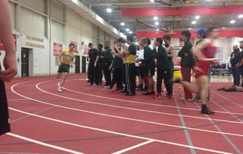 The track team cheers on teammate Brayden Ruland, freshman, as he runs the 4 by 4 relay at the Hinsdale Central meet on Mar. 2.
