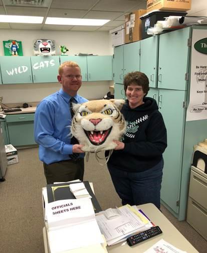 Darren Kobliska, history teacher, passes the Wildcat head to Darlene Castillo, athletic secretary.
