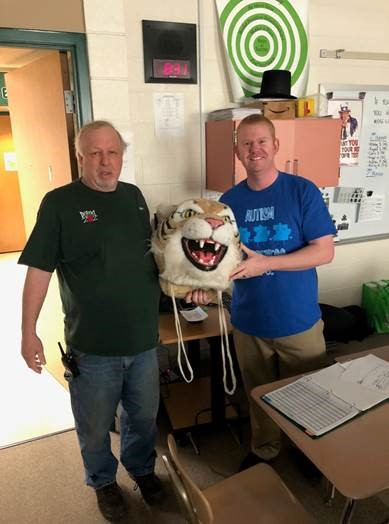 Jeff Pesevanto, custodian, passes the Wildcat Head to Darren Kobliska, history teacher.