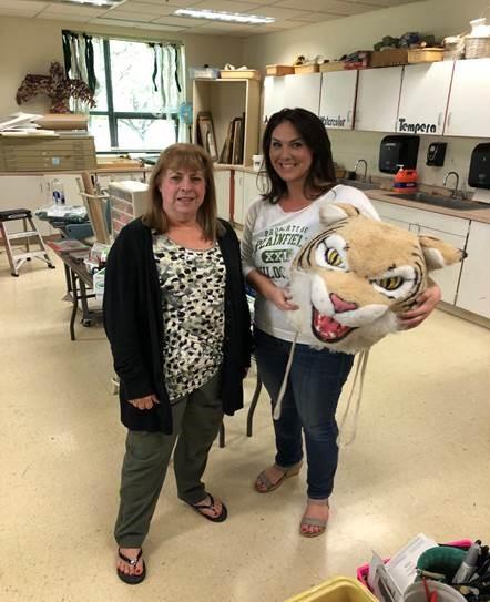 Diane Milligan, secretary, passes the Wildcat head to Lindsey Brown, art teacher.