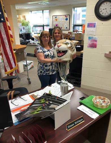 Kathy Rose, special ed secretary, passes the Wildcat head to Diane Milligan, main office secretary.