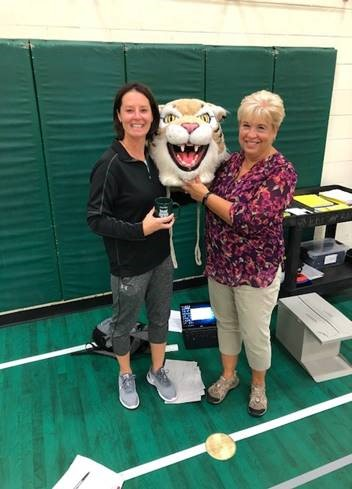 Judy Vihnanek passes the wildcat head to Jen Tomczak, PE department chair