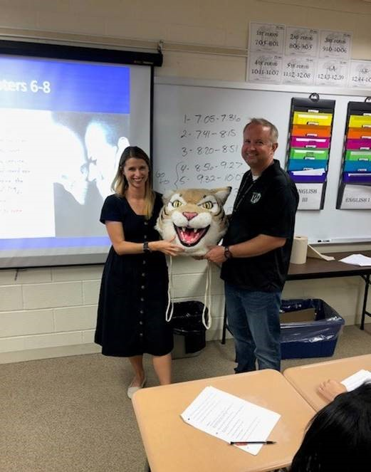 Jerod+Hannon+passes+the+Wildcat+award+to+Ashley+Krause%2C+English+teacher.