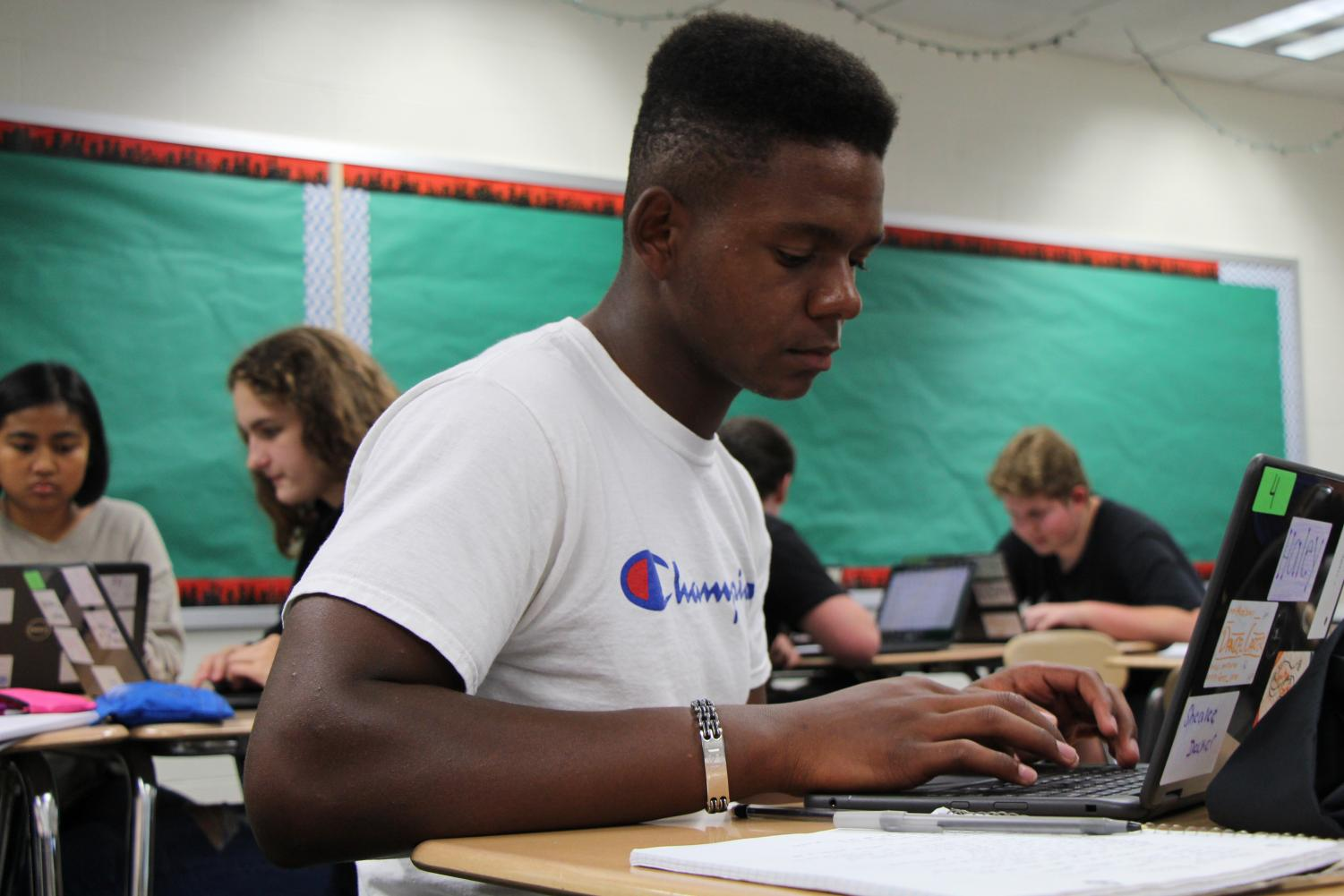 Daniel Carter, senior, works with one of the new laptops to analyze an article for his rhetoric class.