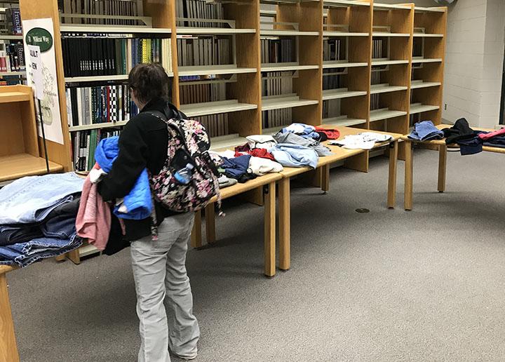A parent chooses clothes from the Wildcat closet during parent teacher conferences.