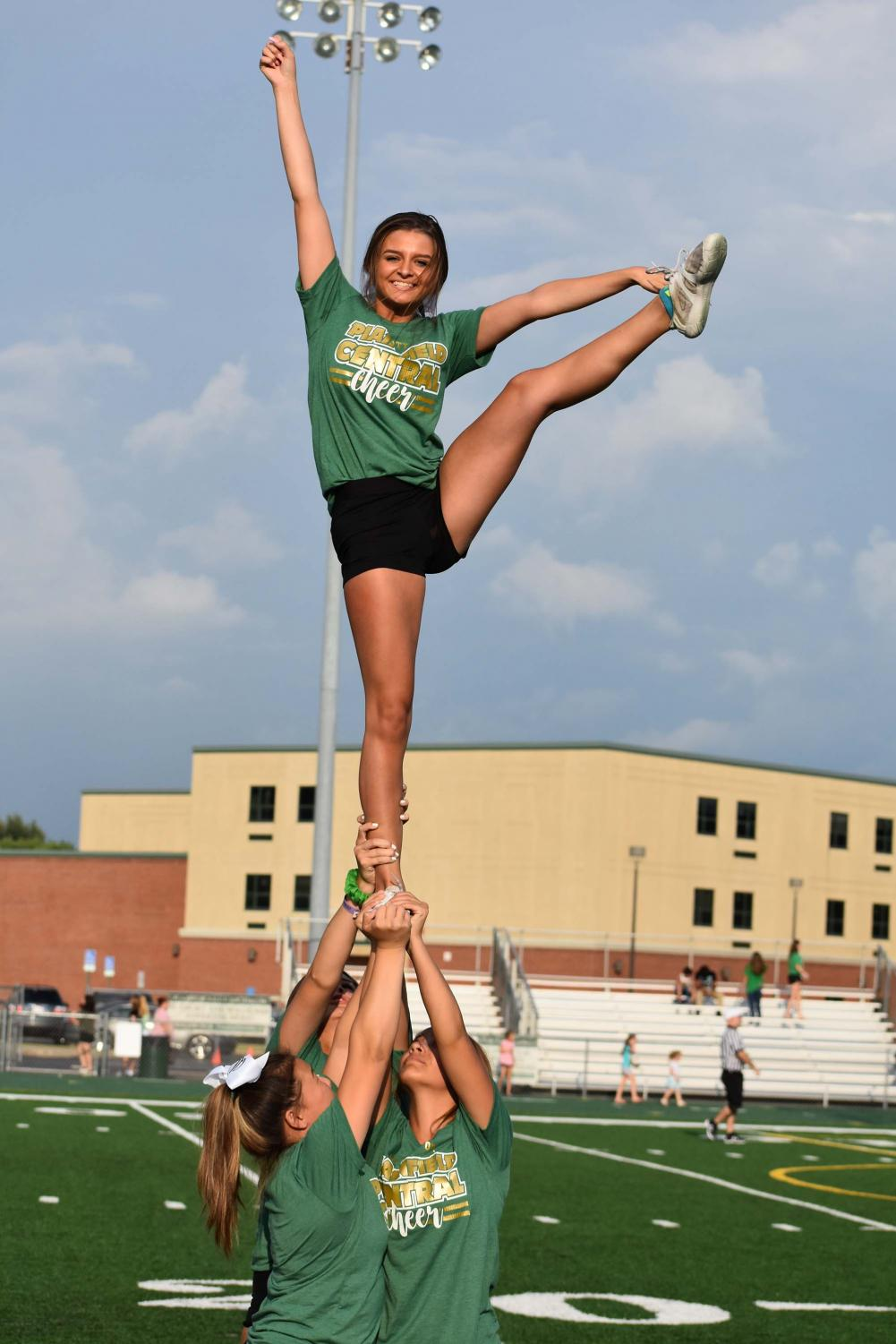 Junior+Katie+Carr+holds+a+heel+stretch+while+in+a+full+extension+stunt+during+the+cheerleading+routine+at+Green+and+White+night.