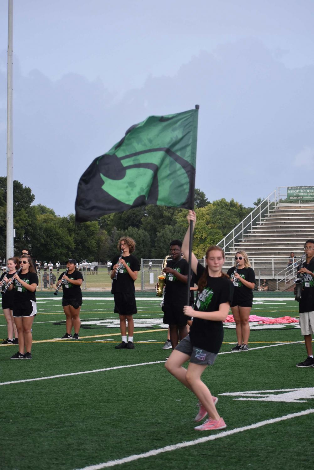 Freshman+Madison+Felgenhauer+marches+with+the+wildcat+flag+during+the+band%27s+half+time+show+performance+%22Double+Agent%22.