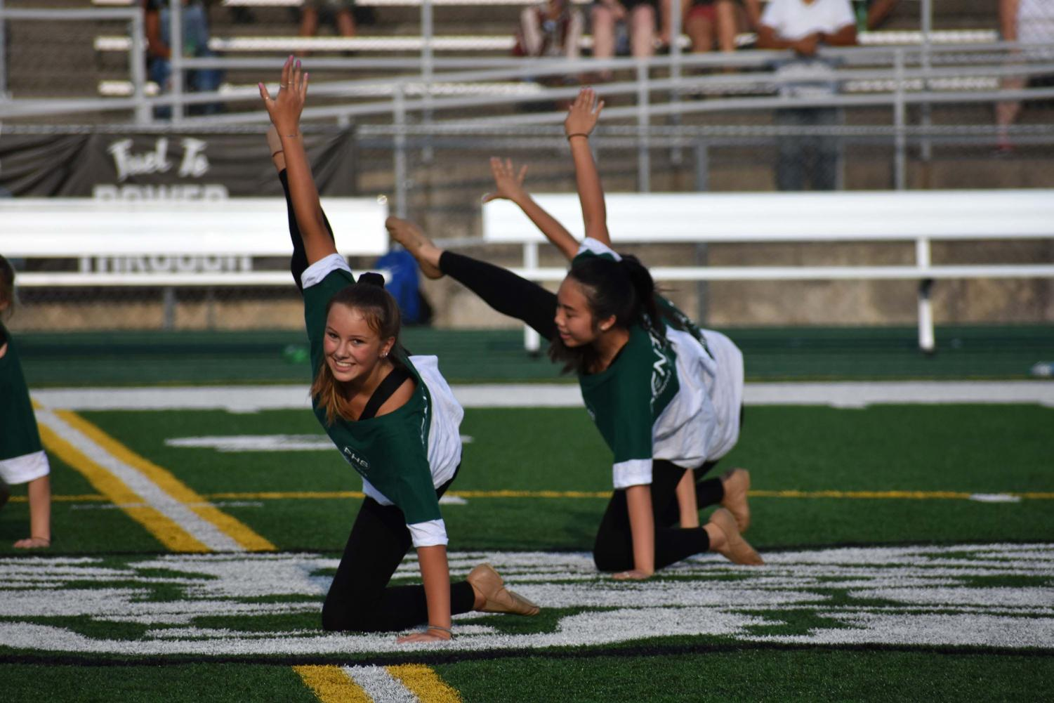 Freshman+Kelly+Loghry+and+sophomore+Crystal+Wong+hit+their+choreography+during+the+combined+JV+and+varsity+green+and+white+night+routine.