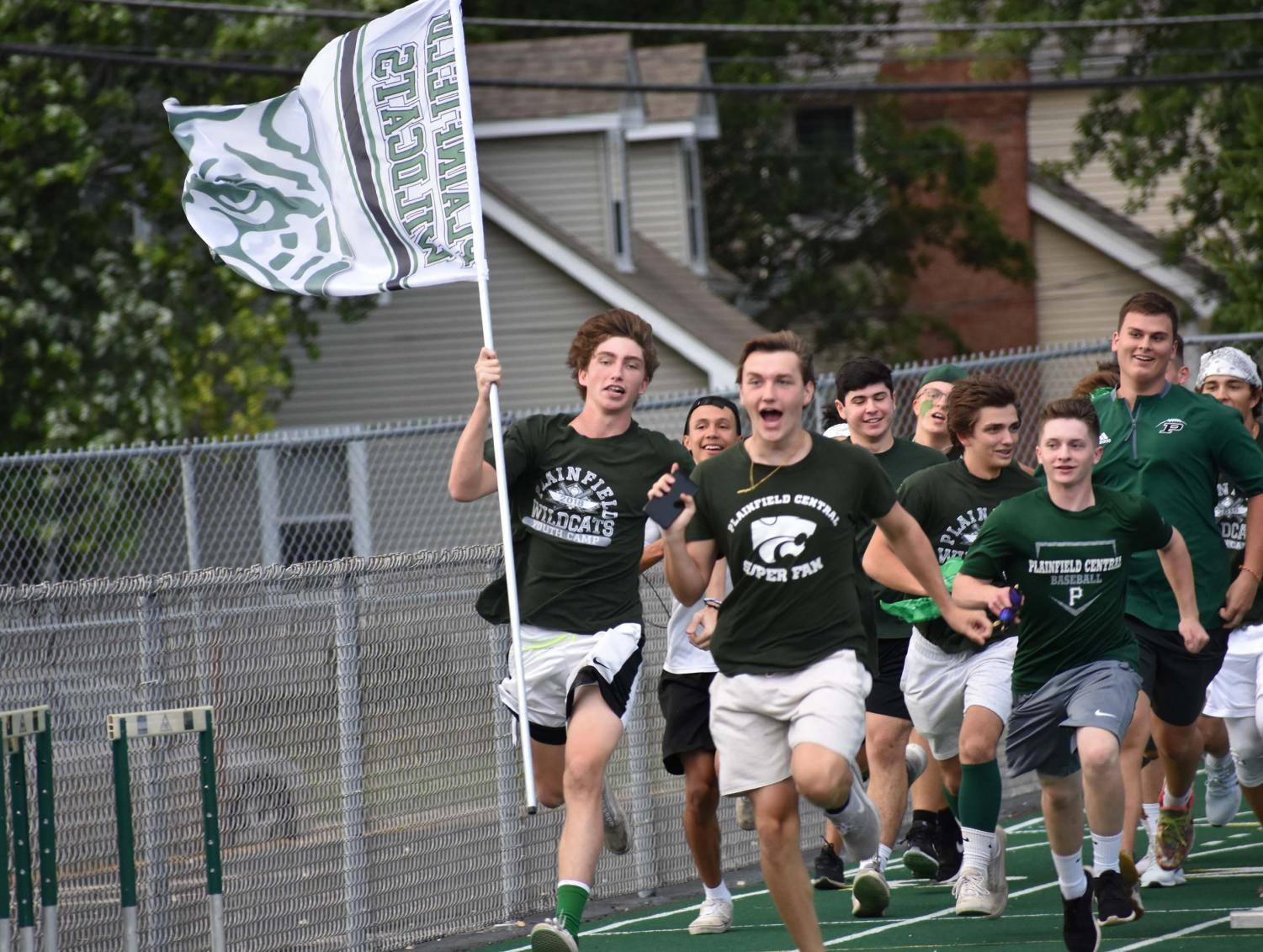 Senior+Billy+Schrage+leads+the+superfans+as+they+run+across+the+track+before+the+varsity+scrimmage.