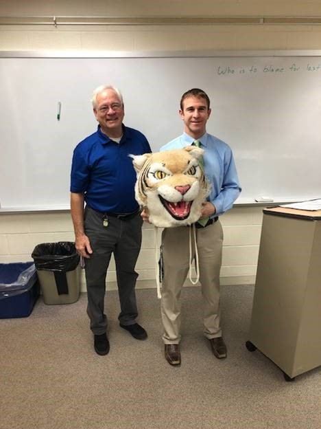 Gary Anton, permanent sub, passes the Wildcat award to Jim Kappas, social studies teacher.