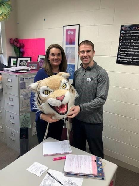 Jim Kappas, social studies teacher, passes the wildcat award to Julie Bortoli, counselor.