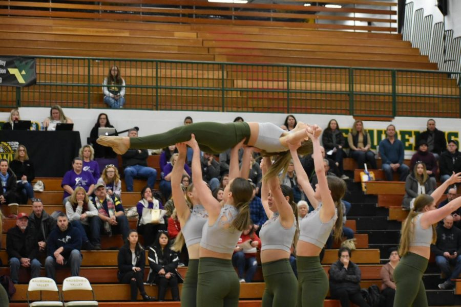 Sophomore Ella Majewski is lifted during the competition routine.