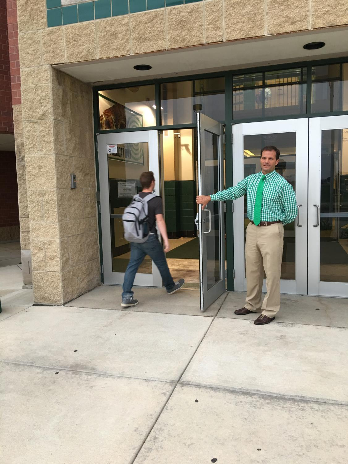 Principal Dave Stephens greets students to start his day. Many appreciate the little things Stephens does to improve the school's atmosphere.