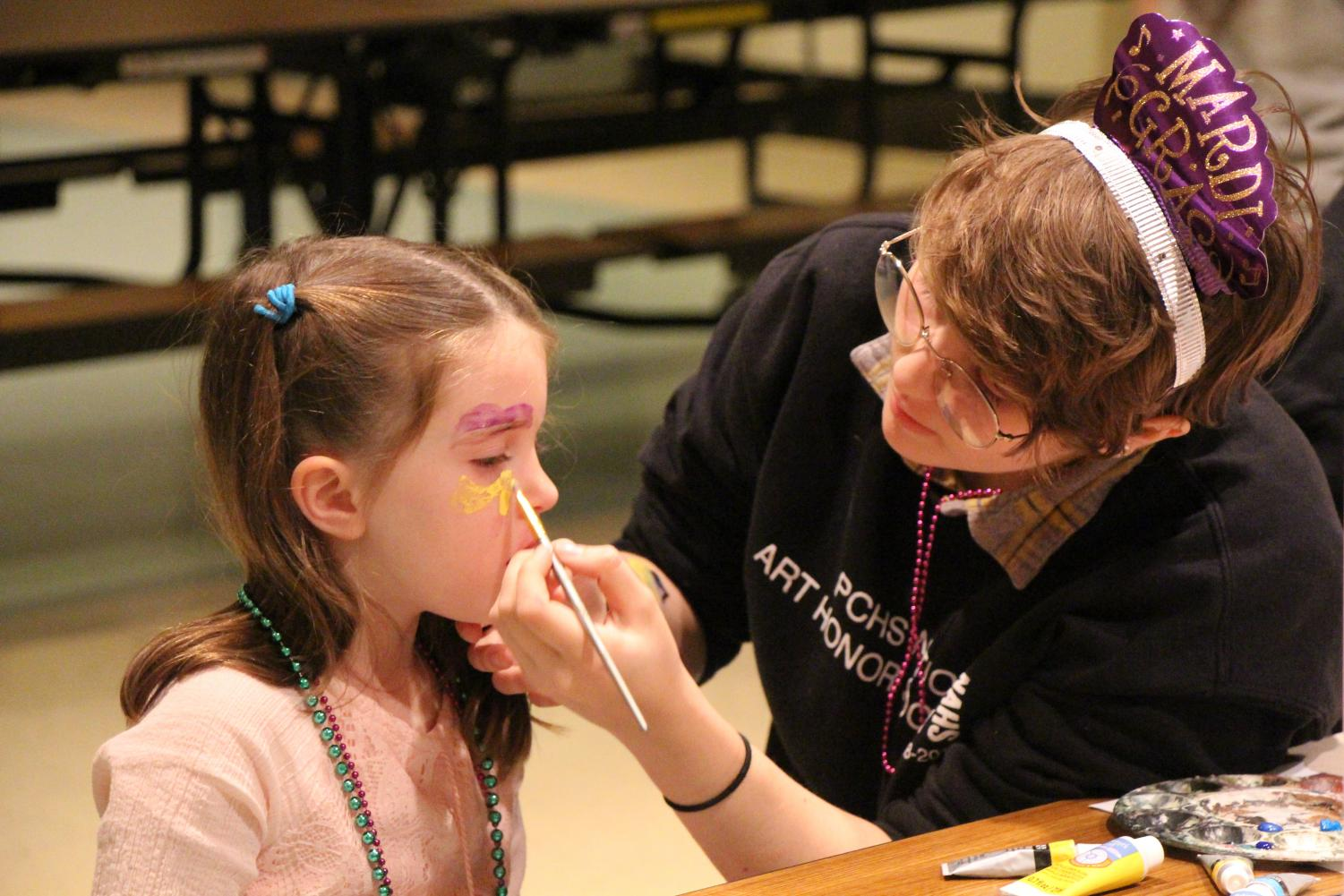 Junior Julia Jessen volunteers at the face painting station for National Art Honor Society at the Mardi Gras celebration in the cafeteria on Tuesday, March 5th.