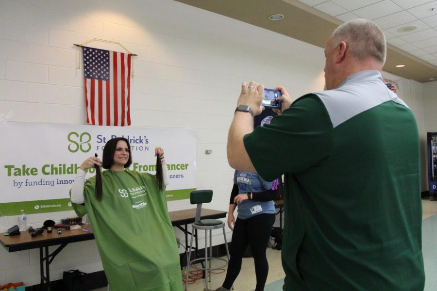 Krusz holds up her chopped locks for a picture by her husband Mark Krusz, Athletic Director.