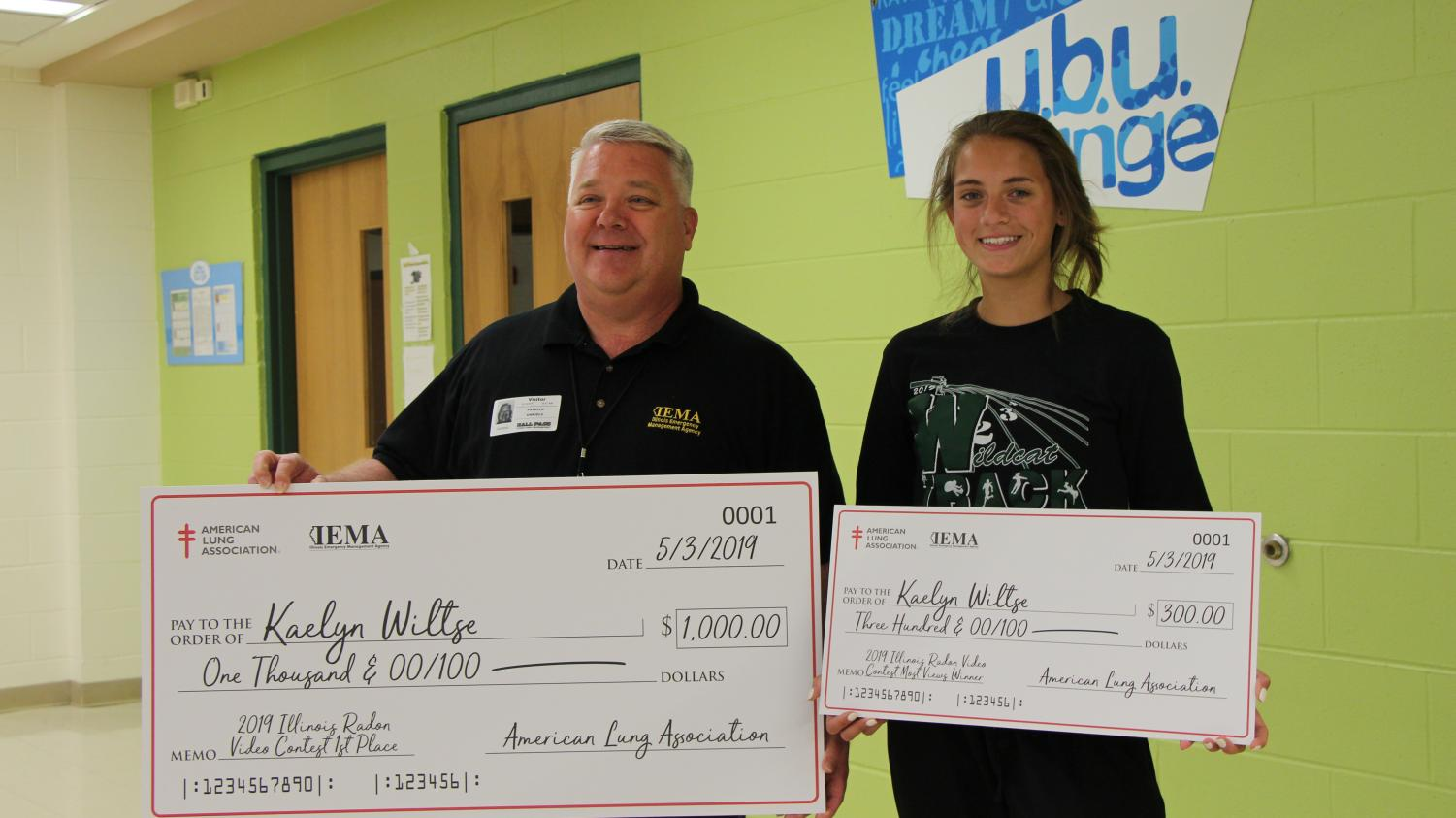 Amaerican Lung Association representative, Pat Daniels (IEMA) holds the $1,000 check for the first place video while senior Kaelyn Wiltze holds the $300 check for most views.