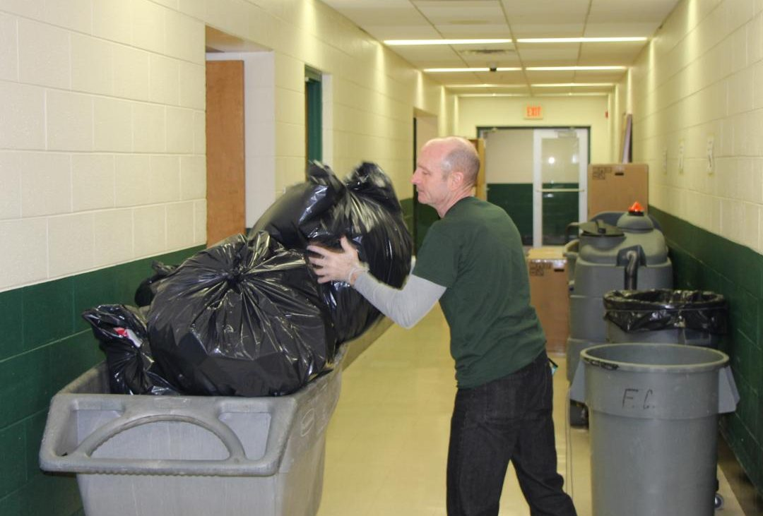 Kevn Codo, custodian,  dumps bags of trash into trash carts each night to have empty cans for the next day.