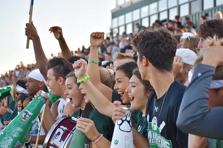 Students+cheer+on+the+football+team+as+they+play+a+game+of+scrimmage.+