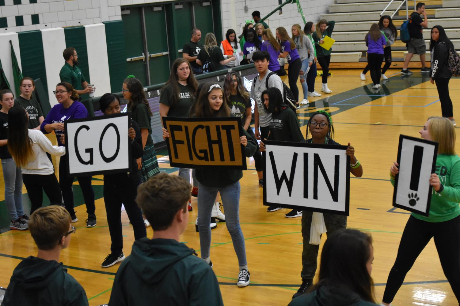 Band Drum Majors Tiara Guider, senior; Paige Gieseke, senior; Jade Price, junior; and Georgia Sigler, senior lead the band in a song while dancing with signs to keep rhythm.