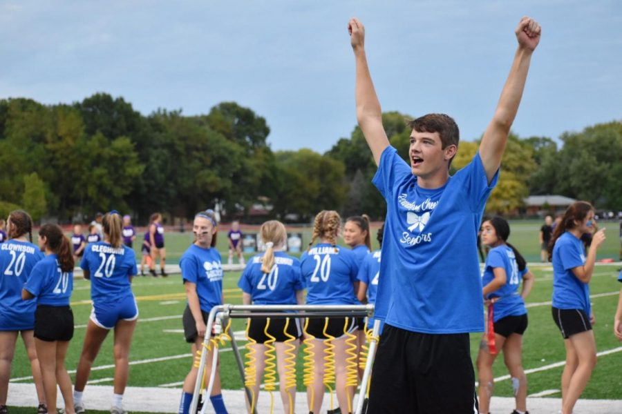 Connor Elens, senior, cheers on his fellow classmates, as boys are cheering for the girls playing football.