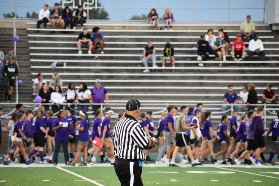 Juniors in purple can be seen behind the referee in between plays.
