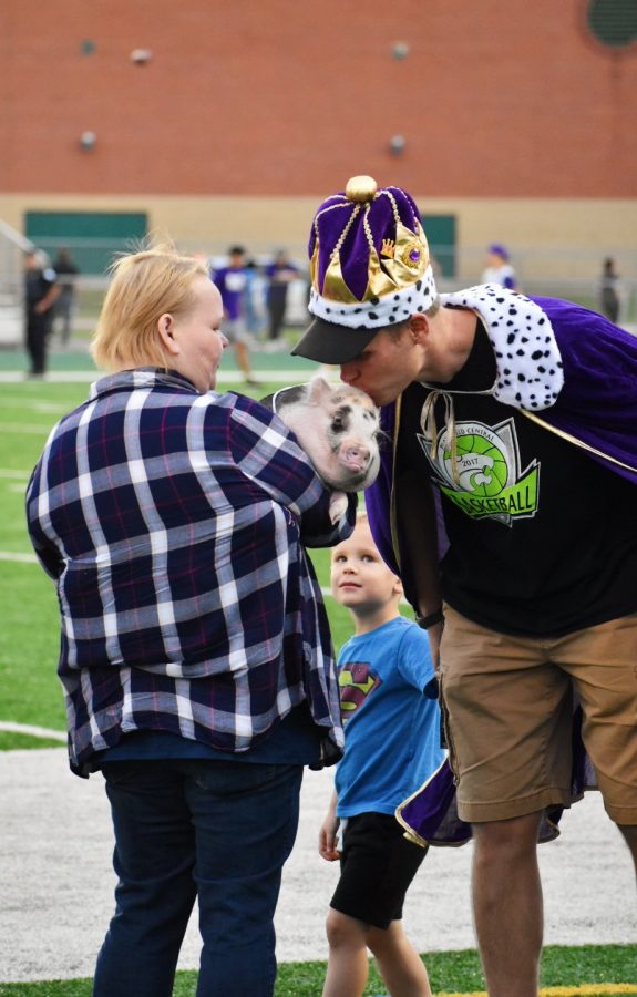 Gregg Bayer, PE teacher, kisses a pig after raising the most money in