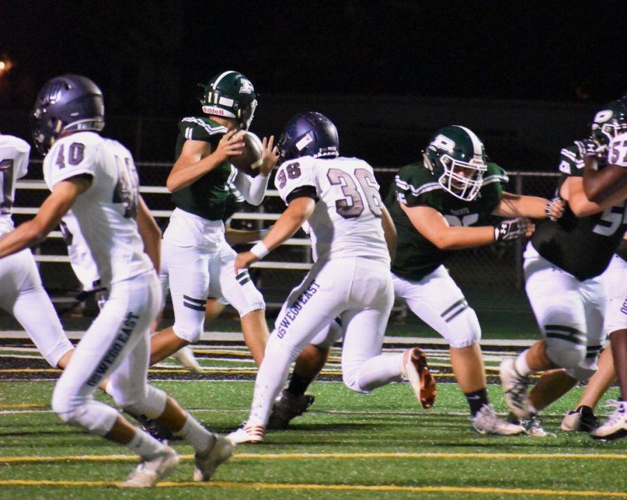 Quarterback Chris Leto (#11), junior, throws a pass to his teammates in their loss against Oswego East 7-55 on Sept. 6