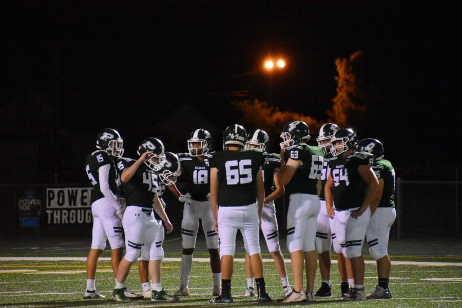 The varsity team huddles to discuss strategies during the fourth quarter.