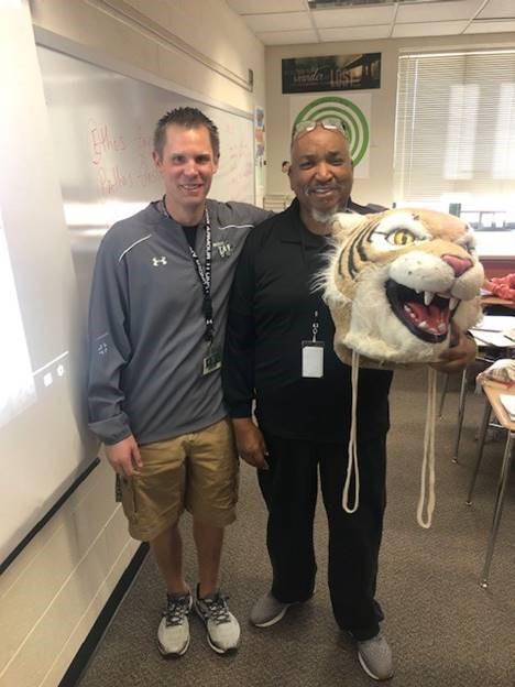 Gregg Bayer, PE teacher, passes the Wildcat Award to John Hill, English teacher.