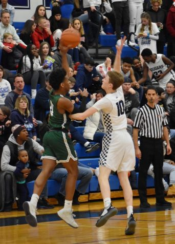 Javari Johnson, senior, passes the ball over the hands of the Plainfield South opponent in their 67-55 win on Friday, Dec 6.