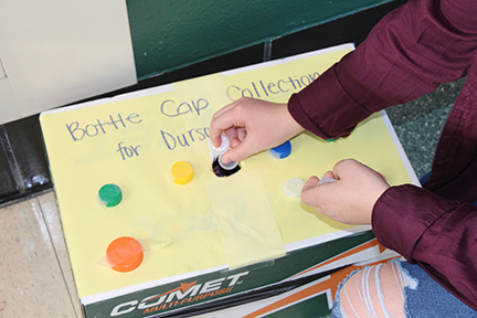 A student donates a bottle cap into the donation box in the front foyer.