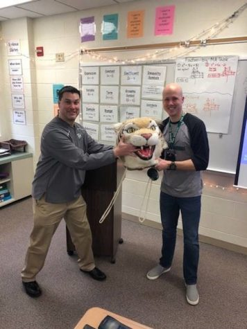 Kevin Fitzgerald, history teacher, passes the Wildcat head to Chris Wells, special ed teacher.
