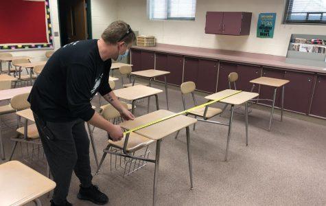 Ben Tuominen, dean's assistant, measures desk spacing to follow proper social distancing guidelines.