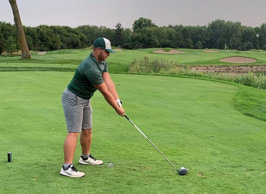 Senior Max Hunter lines up his shot and aims at the hole.