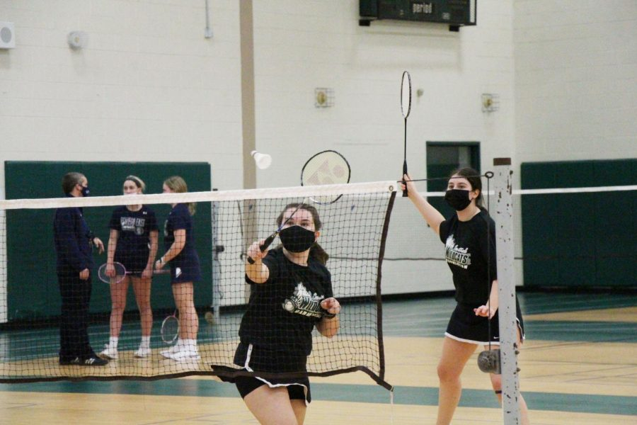 Seniors and doubles partners Sara Rand and Grace Heisen tap a shot over the net.