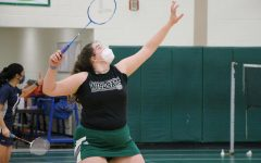Senior, Georgia Jackson, lifts her racket to hit a clear shot.