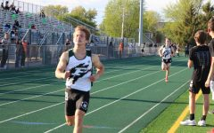 """Michael  Forbear  and  Aaron  Wycoff,  juniors,  cross  the  finish  line  in  the  3200m event at the annual """"Hunt Invitational."""""""
