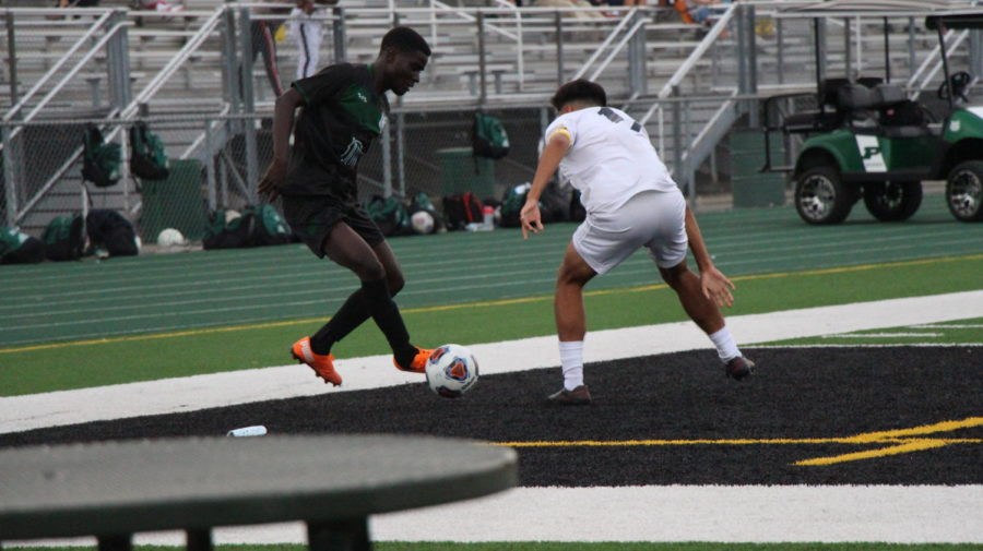Moses+Mata%2C+senior%2C+dribbles+around+a++defender+in+the+Wildcats+2-2+tie+vs.+Plainfield+South+on+Sept.+14.