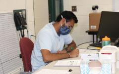 Milan Bhatt, math teacher, wears his mask while he grades students' assignments after class.